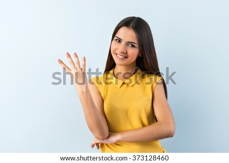 Photo of beautiful young business woman standing near gray background. Smiling woman with yellow shirt looking at camera and showing four fingers - stock photo