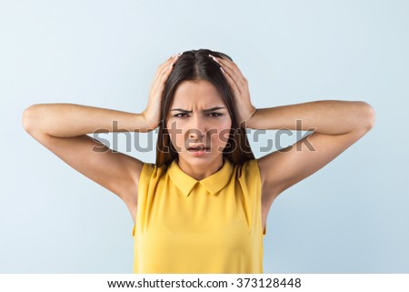 Photo of beautiful young business woman standing near gray background. Stressed woman with yellow shirt having headache - stock photo