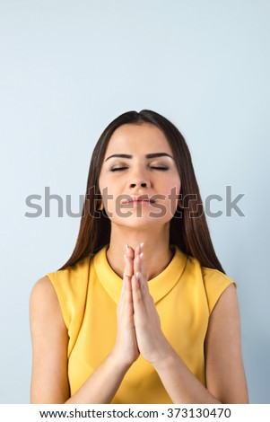 Photo of beautiful young business woman standing near gray background. Woman with eyes closed praying - stock photo