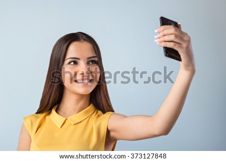 Photo of beautiful young business woman standing near gray background. Woman with yellow shirt making selfie with mobile phone and smiling - stock photo