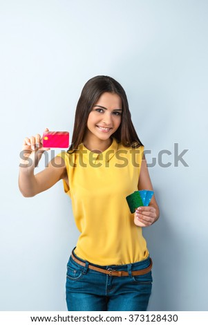 Photo of beautiful young business woman standing near gray background. Woman with yellow shirt looking at camera, smiling and showing credit cards - stock photo