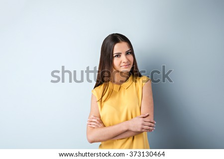 Photo of beautiful young business woman standing near gray background. Woman with yellow shirt looking at camera - stock photo