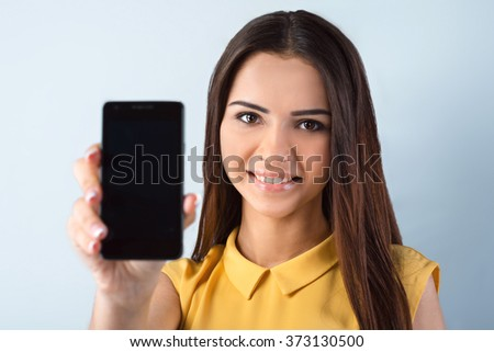 Photo of beautiful young business woman standing near gray background. Woman with yellow shirt looking at camera, smiling and showing mobile phone - stock photo