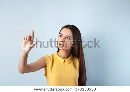 Photo of beautiful young business woman standing near gray background. Woman with yellow shirt looking at screen and pointing at it - stock photo