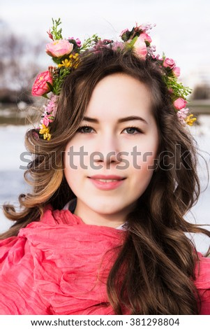 photo of Beautiful young girl with a floral ornament in her hair