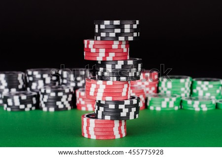 photo of black, red and green casino chips on table