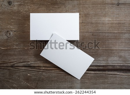 Photo of blank business cards on a dark wooden background. Mock-up for branding identity. Top view. - stock photo