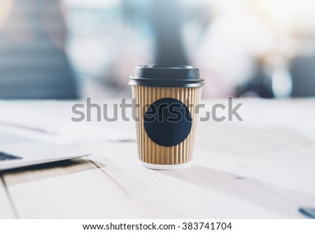 Photo of blank craft paper coffee cup on the wood table. Space for you advertising. Horizontal mockup, blurred background - stock photo
