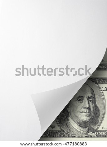 Photo of blank folded sheet of paper with curled corner and hundred dollar bill