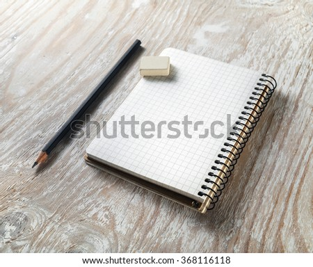 Photo of blank notepaper with pencil and eraser on light wooden background. Template for graphic designers portfolios. Mock-up for branding identity. - stock photo
