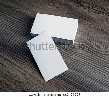Photo of blank white business cards on wooden background. For design portfolios. Blank template for branding identity.