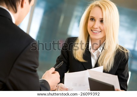 Photo of blond businesswoman looking at her colleague while he explaining his idea