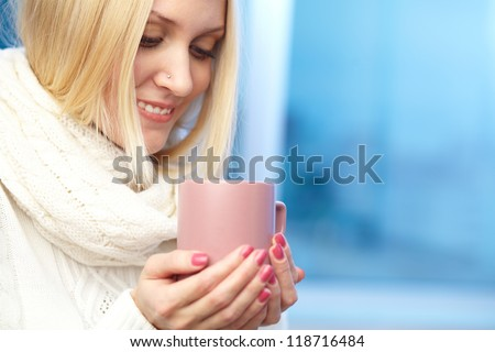 Photo of blond female holding pink porcelain cup and feeling aroma of drink