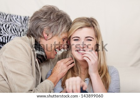 Photo of both grandmother and granddaughter having a funny conversation and giggling together. - stock photo