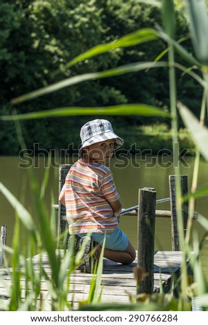 Photo of boy fishing on the lake - stock photo