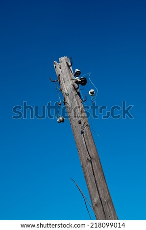 Photo of broken telegraph pole on a saturated blue background - stock photo