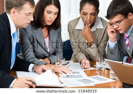 Photo of business group sitting at the table and watching at documents on it with pensive expression - stock photo