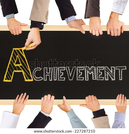 Photo of business hands holding blackboard and writing ACHIEVEMENT concept - stock photo