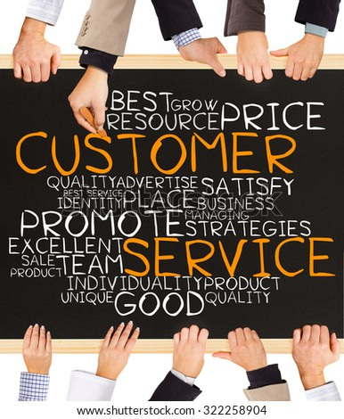 Photo of business hands holding blackboard and writing CUSTOMER SERVICE word cloud - stock photo