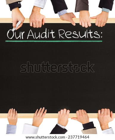 Photo of business hands holding blackboard and writing Our Audit Results - stock photo