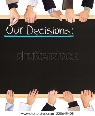 Photo of business hands holding blackboard and writing Our Decisions - stock photo