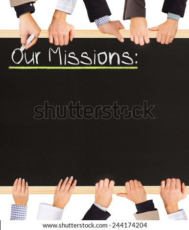 Photo of business hands holding blackboard and writing Our Missions - stock photo