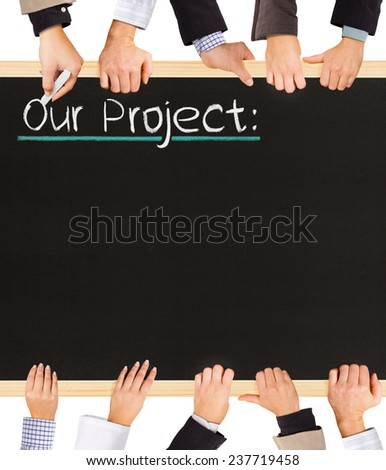 Photo of business hands holding blackboard and writing Our Project - stock photo