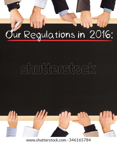 Photo of business hands holding blackboard and writing Our Regulations in 2016 - stock photo