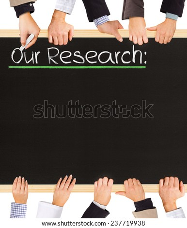 Photo of business hands holding blackboard and writing Our Research - stock photo
