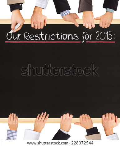 Photo of business hands holding blackboard and writing Our Restrictions for 2015 - stock photo