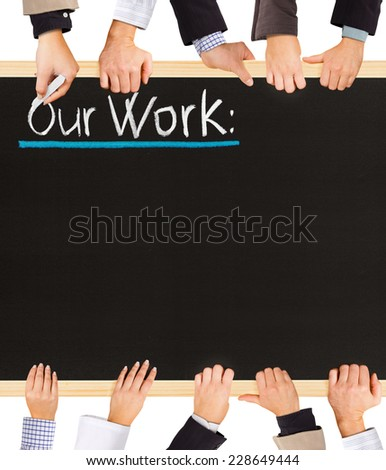 Photo of business hands holding blackboard and writing Our Work - stock photo
