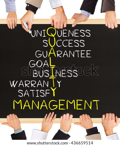 Photo of business hands holding blackboard and writing QUALITY MANAGEMENT concept - stock photo
