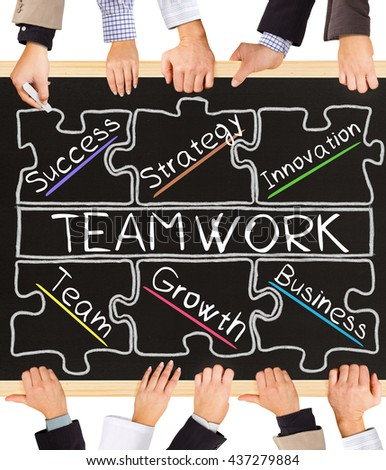 Photo of business hands holding blackboard and writing TEAMWORK concept - stock photo
