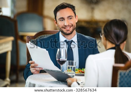 Photo of business meeting in expensive hotel. Young smiling businessman talking with business woman and showing documents while having dinner - stock photo