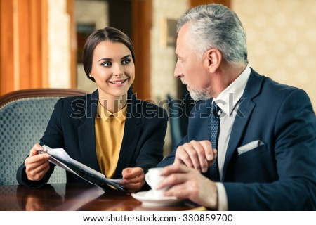 Photo of business meeting in expensive hotel. Young smiling businesswoman showing documents to adult businessman while drinking coffee