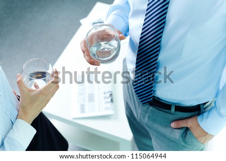 Photo of business partners hands holding glasses with water - stock photo
