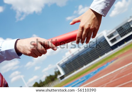 Photo of business people hands passing baton during marathon - stock photo