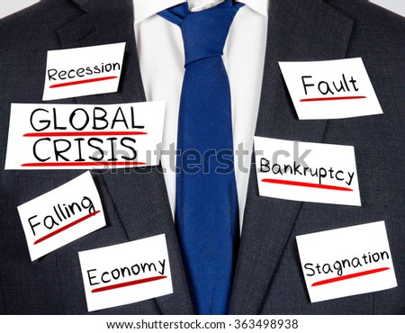 Photo of business suit and tie with GLOBAL CRISIS conceptual words written on paper cards - stock photo