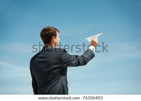 Photo of businessman holding paper aircraft in stretched hand before launching it - stock photo