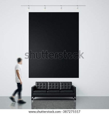 Photo of businessman in gallery. Waching empty black canvas hanging on the brick wall and generic design sofa concrete floor. Square, blank mockup. Motion blur