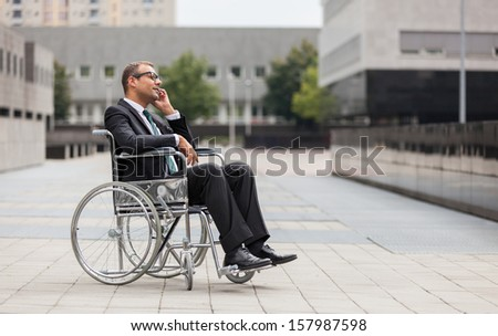 Photo of businessman on wheelchair who is phoning - stock photo