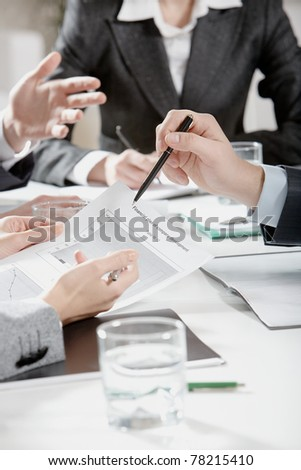 Photo of businesspeople?s hands holding papers and pens over workplace