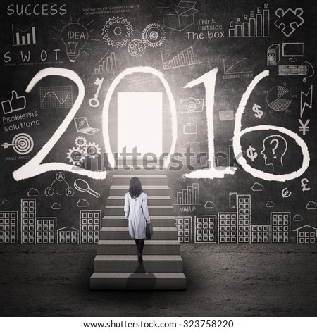 Photo of businesswoman walking on the stairs toward a door with numbers 2016 and scribble - stock photo