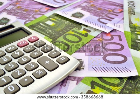 Photo of calculator with money 100 and 500 euro