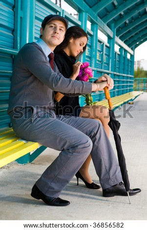 Photo of calm man looking aside with his girlfriend near by during their date outdoors