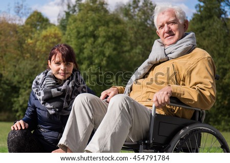 Photo of caregiver and positive elderly man on wheelchair - stock photo