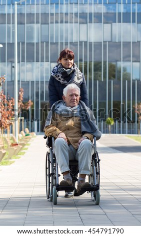 Photo of carer and elderly man on wheelchair during trip - stock photo