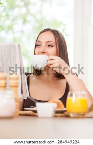 Photo of caucasian brunete woman reading a newspaper while having breakfast at home - stock photo