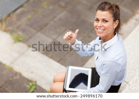 Photo of caucasian smiling businesswoman sitting outdoor and making positive thumb gesture - stock photo