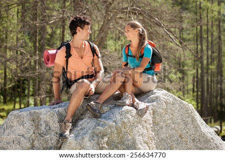 Photo of caucasian young couple relaxing on a big rock in the mountains - stock photo